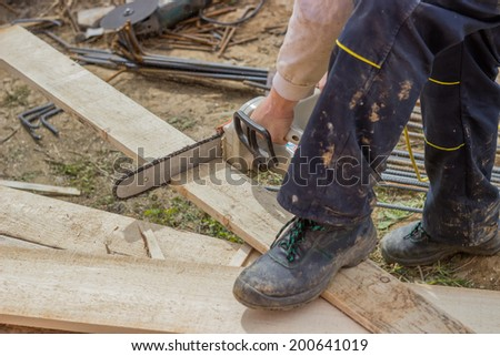 Builder worker cutting wooden plank with chainsaw at construction site. Focus on chainsaw.