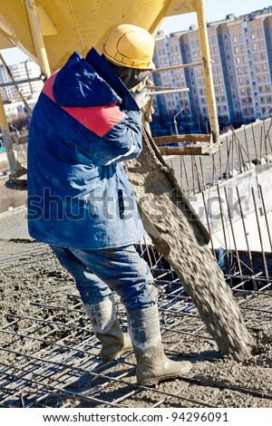 builder worker in hard helmet  and uniform during concrete pouring works at construction site - stock photo
