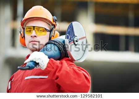 builder worker in safety protective equipment with grinding machine power tool at construction site - stock photo