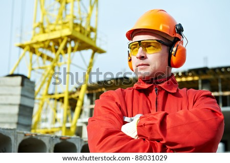 builder worker in uniform and safety protective equipment at construction site - stock photo