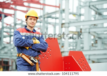 builder worker in uniform and safety protective equipment at construction site in front of metal construction frames - stock photo