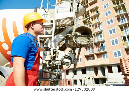 builder worker in uniform in front of concrete mixer truck at construction site - stock photo