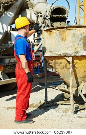 builder worker in uniform with in front of concrete mixer at construction site