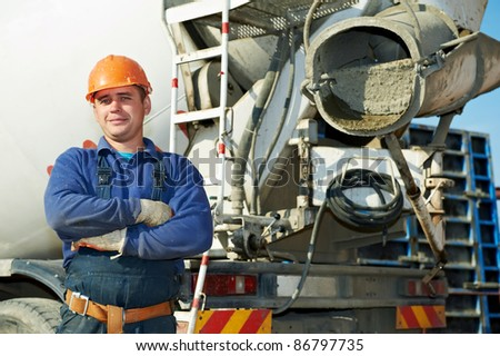 builder worker in uniform with in front of concrete mixer at construction site - stock photo