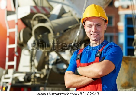 builder worker in uniform with in front of concrete moxer at construction site - stock photo