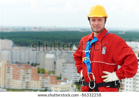 builder worker in uniform with safety belt at construction site - stock photo