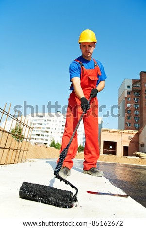 builder worker in uniformcovering roof with insulation tar material at construction site - stock photo