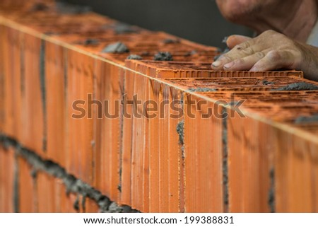 Builder worker installing clay block wall, lay clay block. Selective focus and motion blur. - stock photo