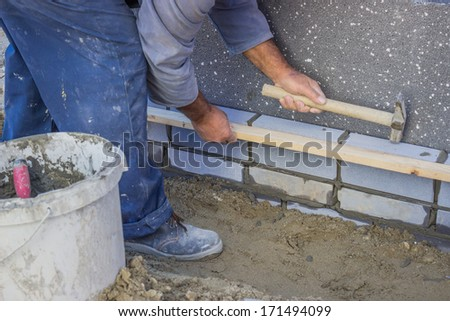Builder worker installing insulation layer. Brick support systems supplied insulation layer to minimise heat loss, and improve the energy efficiency of a building.   - stock photo
