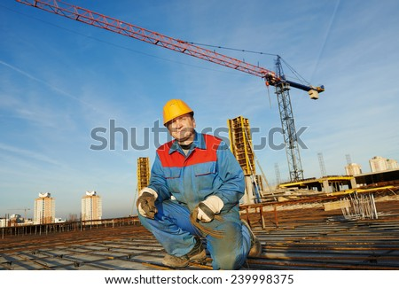builder worker knitting metal rebars into framework reinforcement for concrete pouring at construction site - stock photo