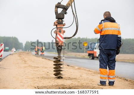 Builder worker monitoring drilling holes in ground during construction road works - stock photo