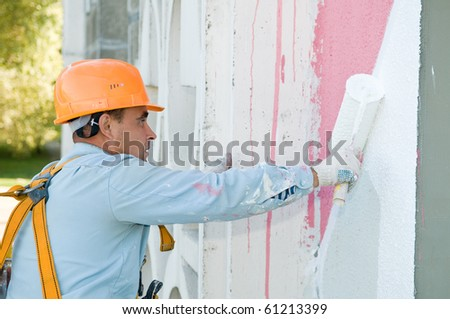 builder worker painting facade of building house with roller