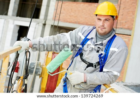 builder worker painting facade of building with roller - stock photo