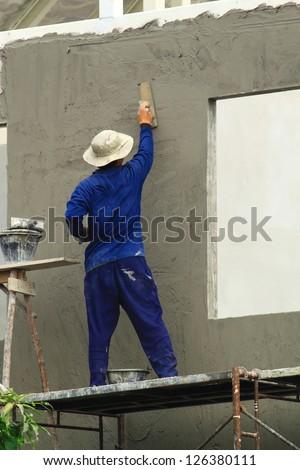Builder worker plastering - stock photo