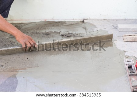 Builder worker plastering concrete at floor of house construction - stock photo