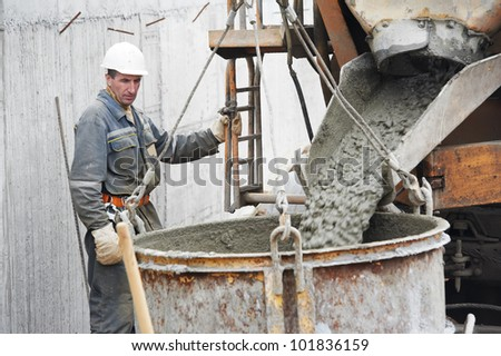 Builder worker pouring concrete from automobile mixer into construction barrel - stock photo
