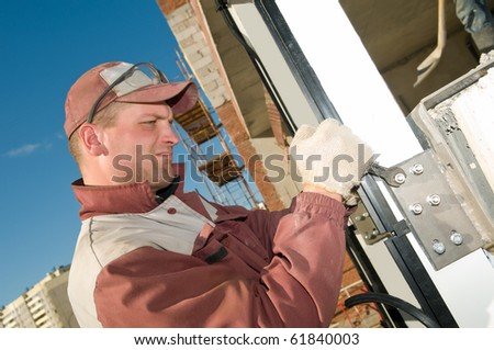 Builder worker tightening the screws at construction site with wrench - stock photo