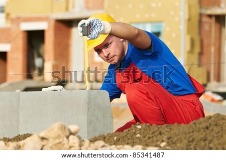 Builder worker using measure tape at construction site - stock photo