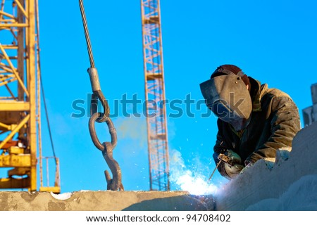 Builder worker welder during installation of house wall panels using blind welding machine and tower crane - stock photo