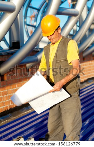 Builder worker with blue print at construction site - stock photo