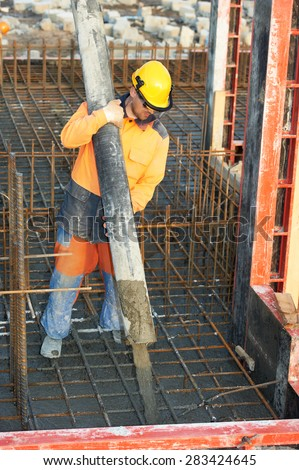 builder worker with boom pump pouring concrete on metal rods reinforcement of formwork - stock photo