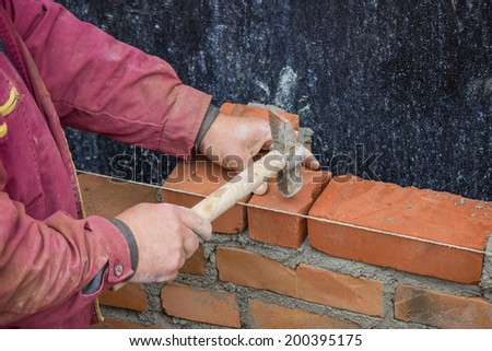 Builder worker with bricklayer hammer laying solid clay brick, bricklaying - stock photo