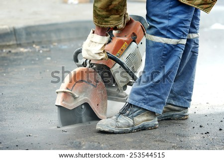 Builder worker with cut-off machine power tool breaking asphalt at road construction site - stock photo