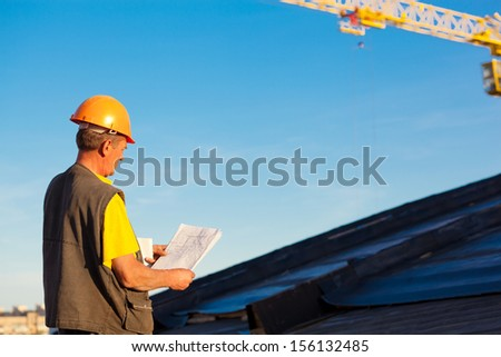 Builder worker with drawing at construction site - stock photo