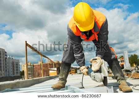 Builder worker with grinder machine cutting metal parts at construction site - stock photo