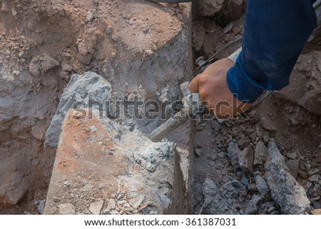 Builder worker with hammer drill equipment breaking for construction site - stock photo