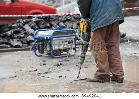 Builder worker with pneumatic hammer drill equipment breaking asphalt at construction site - stock photo