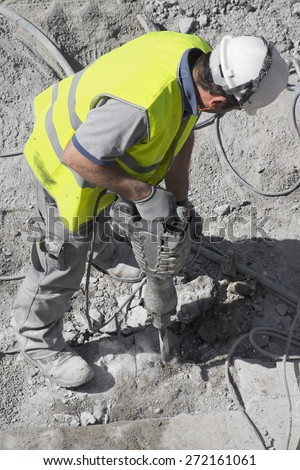 Builder worker with pneumatic hammer drill equipment breaking sidewalk at city - stock photo