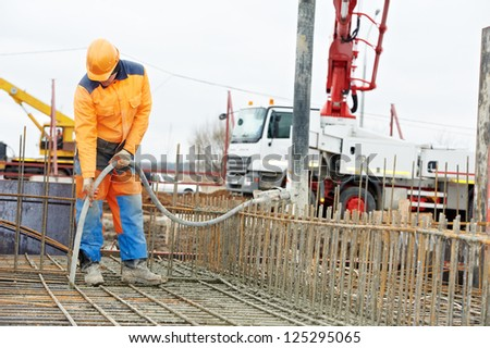 builder worker with vibrator machine compacting poured concrete into reinforcement formwork - stock photo