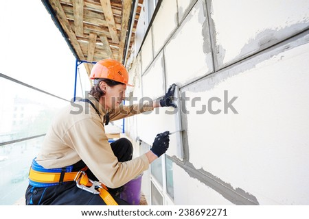 builder worker works with facade joint of building with plaster and spatula