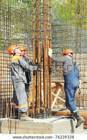 builder workers installing metal rods bars into framework reinforcement for concrete pouring at construction site - stock photo