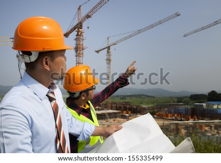 Builder workers partners looking at new construction plan and discussing it - stock photo