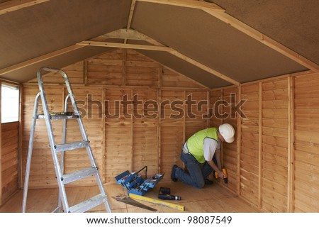 builder working in wooden construction with power tools in protective clothing - stock photo