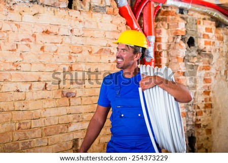 Builder working on construction site with hose over his shoulder