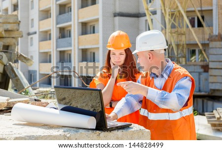 builders at work with a laptop on the background of construction - stock photo