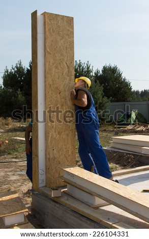 Builders positioning an upright wall panel with thick insulation on a construction site for a new build home - stock photo