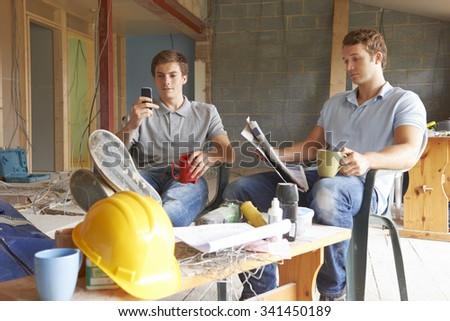 Builders Relaxing During Break On Site - stock photo