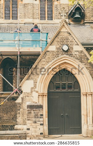 Builders repairing roof of a church standing on scaffolding, church door in foreground - stock photo