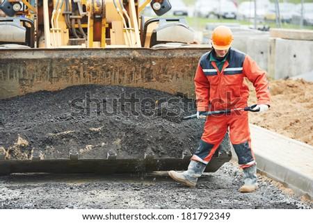 builders workers at asphalting paver machine during Road street repairing works - stock photo
