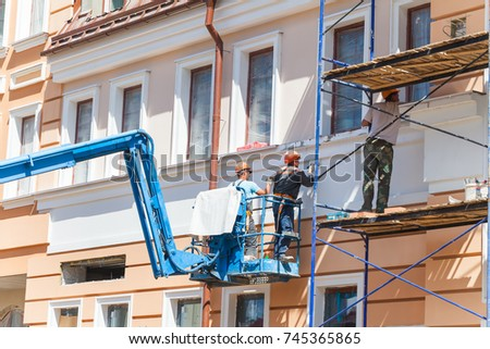 Builders working in helmets on a hydraulic lift plaster the wall of the building.Belarus, Minsk, May 2017