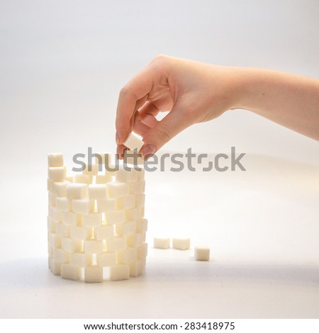 building a cylinder tower from sugar cubes - stock photo