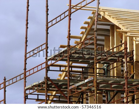 Building a new house; scaffolding and unfinished roof - stock photo