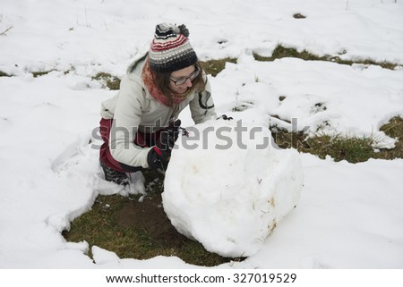 building a snowman together in winter landscape