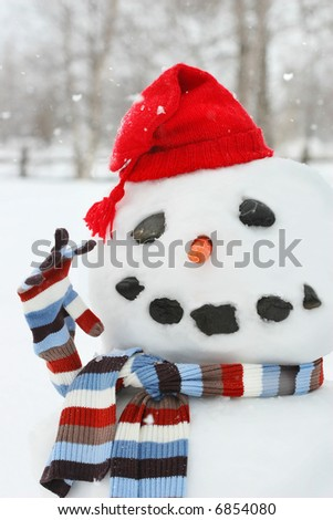 Building a snowman with red hat on a cold snowy day - stock photo