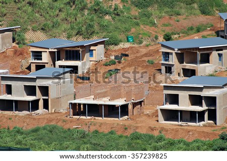 Building and construction sites in progress to new houses in a housing estate in South Africa. - stock photo