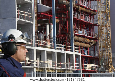 building and contruction worker with large industrial plant - stock photo